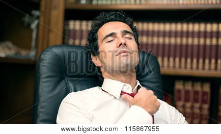 Businessman loosing his necktie after an hard working day