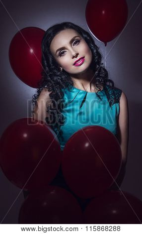 Happy young woman with red latex balloons
