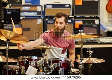 male musician playing cymbals at music store