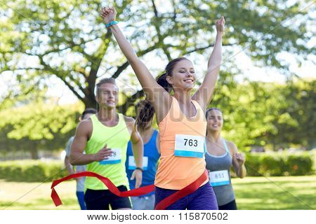 happy young female runner winning on race finish