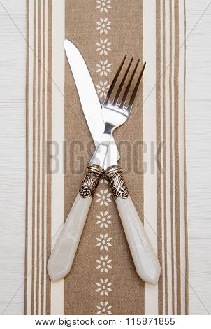 Knife And Fork At Napkin On White Wooden Background