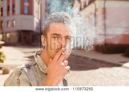 Close Up Portrait Of Handsome Man Smoking Cigarette