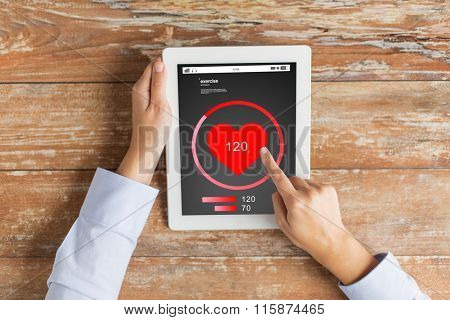 close up of hands with heartbeat on tablet pc