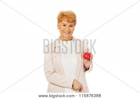 Smile elderly woman holding heart model
