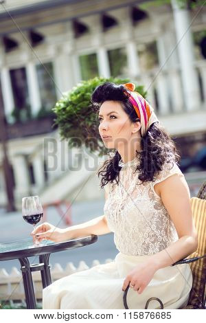 Young Italian woman drinking red wine in an outdoor cafe