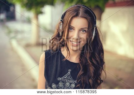 Young beautiful girl listening to MP3 player on the street