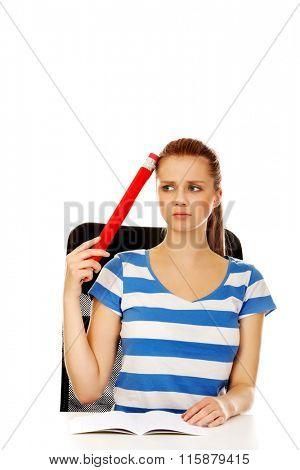 Teenage woman doing homework and holding huge pen