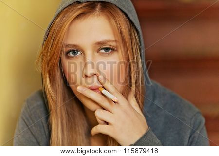 Teenage woman sitting on stairscase and smoking cigarette