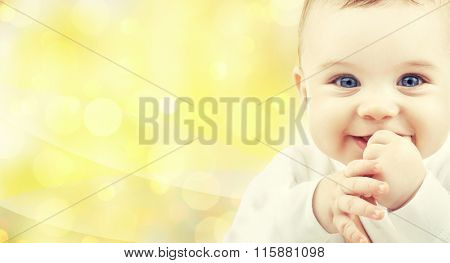 close up of happy baby over yellow background