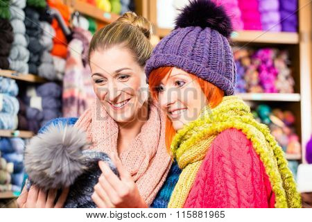 Young women buying colorful bobble hat in knitting fashion textile store