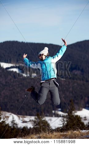 girl jumping in wintertime. Mountain background