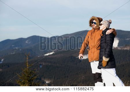 Happy couple enjoying mountain view together in wintertime.