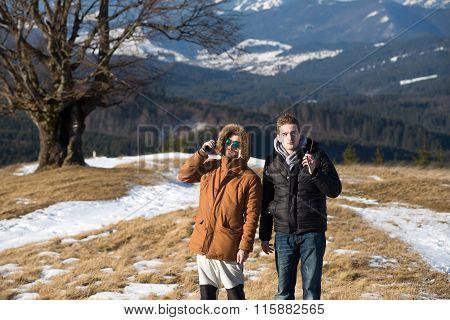 Male hikers using walkie talkie against mountain peaks