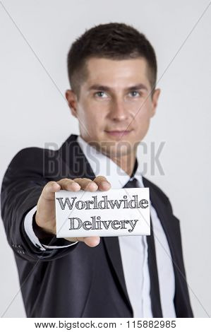 Worldwide Delivery - Young Businessman Holding A White Card With Text