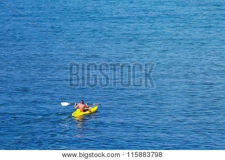Young caucasian man kayaking in sea