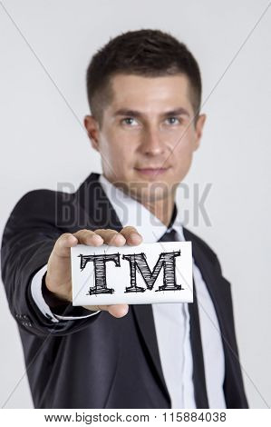 Tm Trade Mark - Young Businessman Holding A White Card With Text
