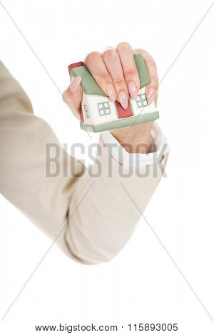 Angry businesswoman crushing small house.