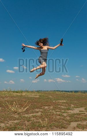 Barefooted Girl Jumping With Her Shoes