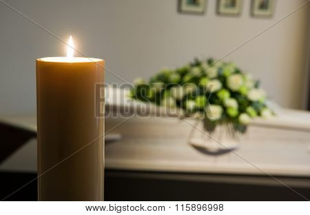 Burning Candle In Front Of Coffin