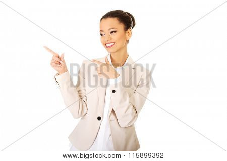 Happy businesswoman pointing up.
