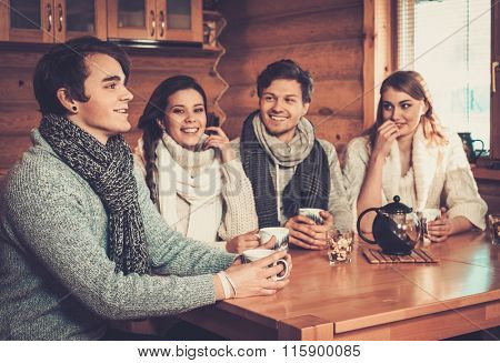 Young couples drinking hot tea in cosy winter cottage kitchen.