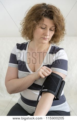 woman checking  blood pressure by tonometer.