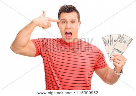 Young man holding money and his hand against his head making a gun gesture isolated on white background