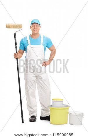 Full length portrait of a young male decorator holding a paint roller and looking at the camera isolated on white background