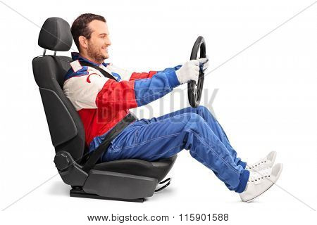 Profile shot of a young car racer holding a steering wheel and pretending to drive isolated on white background
