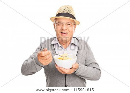 Studio shot of a cheerful senior gentleman eating cereal from a bowl isolated on white background