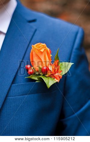 boutonniere of orange roses in the pocket of his jacket male.