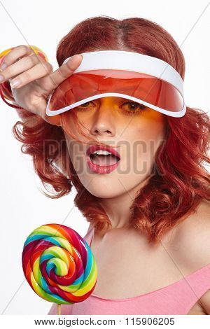 Bright makeup. Girl Portrait holding Colorful lollipop. Pink cap.