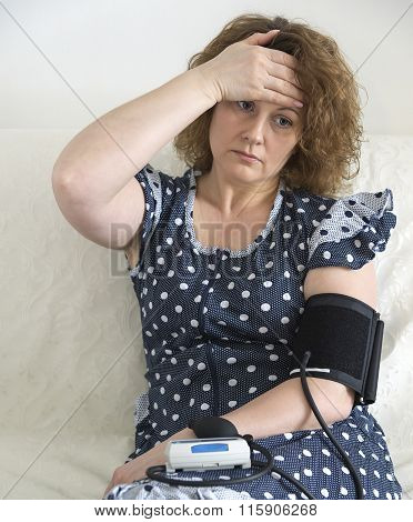 Woman with headache measures blood pressure