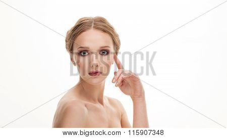 Closeup beauty portrait of young adorable blonde woman touching her cheekbone by finger on white stu