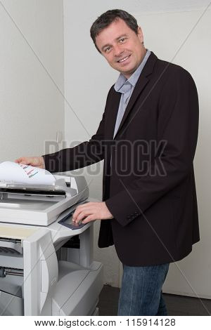 Side View Of Businessman Keeping Paper On Photocopy Machine