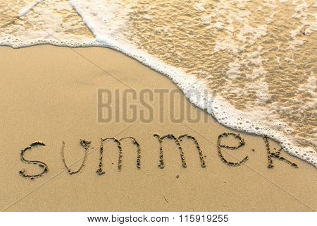 SUMMER written on the beach sand with a soft rolling wave.