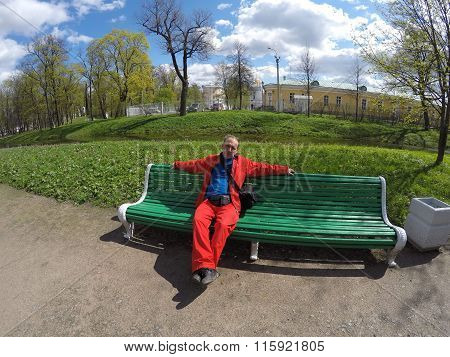 The man in a red sports suit on a bench in spring park.