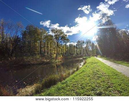 Beautiful bright summer landscape - the road along the river and the wood under the blue sky