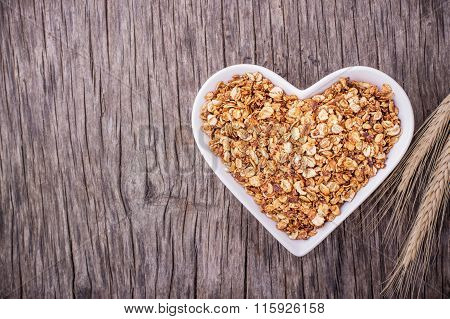 Home caramel granola in a white ceramic dish shape of heart
