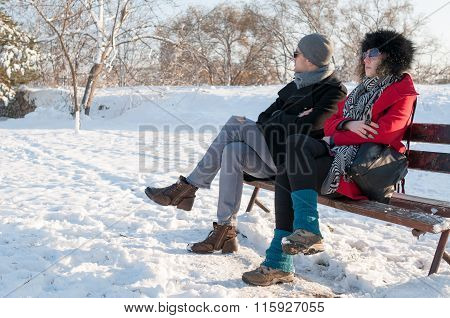Couple Sitting On Bench In Winter