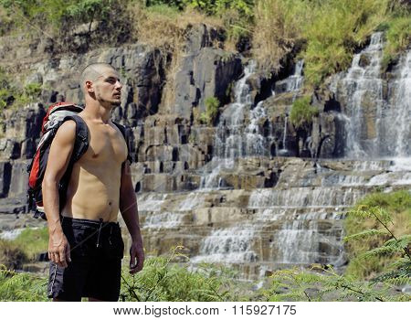 mature man with backpack at waterfall pongour close up, looking for view