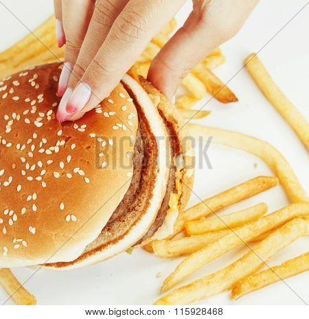 woman hands with manicure holding hamburger and french fries isolated on white, food unhealthy