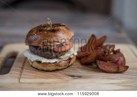 Burger with meat cutlet is on the board and chips
