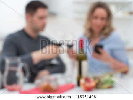 Young couple having dinner at home. Modern relationships. Blurred image.