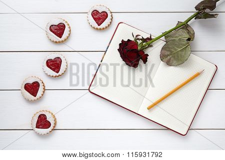 Heart shaped cookies with empty notebook, pencil and rose flower on white wooden background for Vale