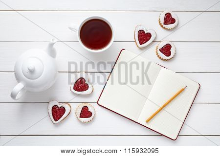 Homemade heart shaped cookies with empty notebook, pencil, cup of tea and teapot on white wooden bac