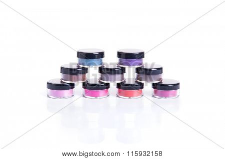 Set of bright mineral eye shadows in transparent jars, isolated on white background