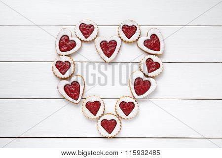 Heart of the shortbread heart-shaped cookies with jam on white wooden table background.