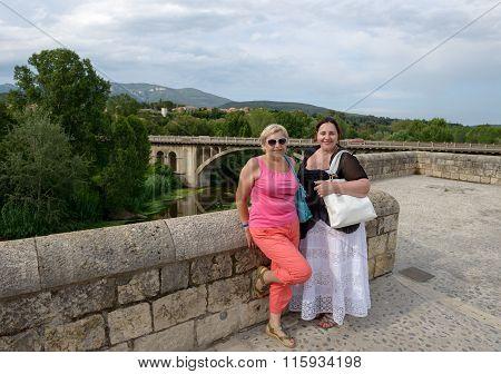 Tourist Women On Old Bridge Of Besalu, Catalonia, Spain.