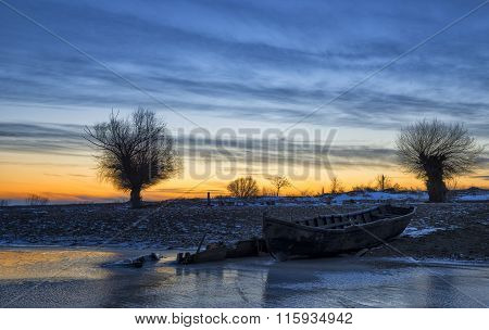 Old Boat At Sunset On The Danube River In Winter